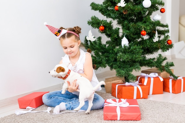 Koncepcja boże narodzenie, zwierzęta domowe i święta - dziecko w santa hat z szczeniakiem jack russell terrier.