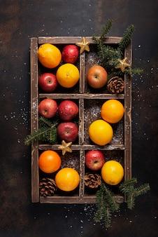 Koncepcja bożego narodzenia. drewniane pudełko z pomarańczą, jabłkiem i szyszkami ze świątecznymi dekoracjami. widok z góry na dół
