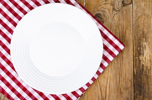 Koncepcja bożego narodzenia i nowego roku. biały talerz, czerwony obrus.