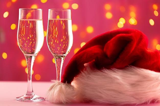 Koncepcja bożego narodzenia i nowego roku z dwoma kieliszkami szampana przed światłami bokeh