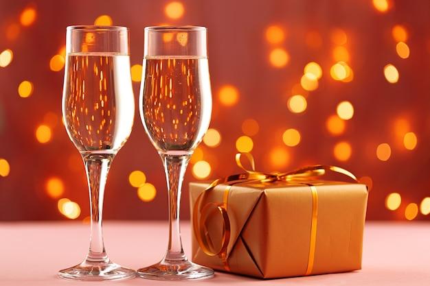 Koncepcja bożego narodzenia i nowego roku z kieliszkami szampana przed światłami bokeh