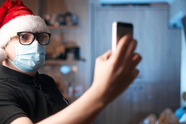 Koncepcja bożego narodzenia, kaukaski mężczyzna w masce medycznej i santa hat