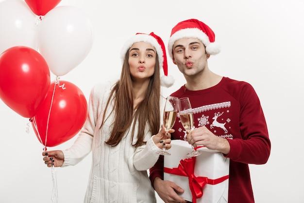 Koncepcja bożego narodzenia - młoda dziewczyna trzyma balon i szampana, grając i świętując ze swoim chłopakiem w boże narodzenie.