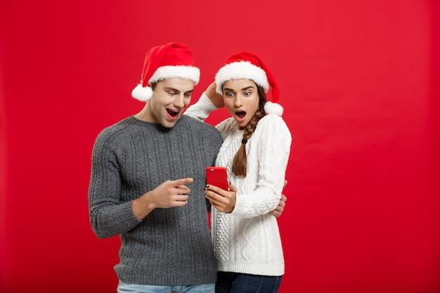Koncepcja bożego narodzenia - młoda para przystojny i piękny cieszyć się sprawdzaniem na telefonie komórkowym w boże narodzenie.