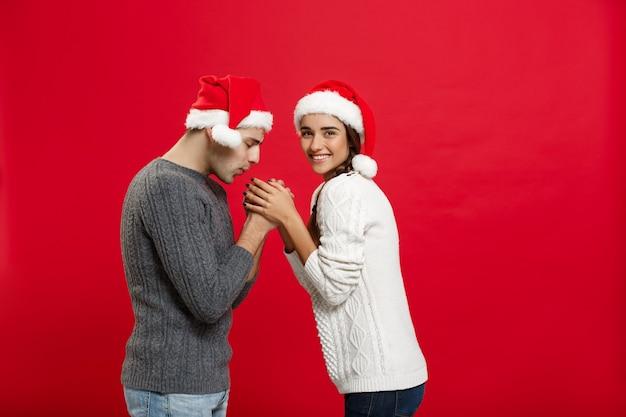 Koncepcja bożego narodzenia - młoda para stylowe trzymając się za ręce w zimie.