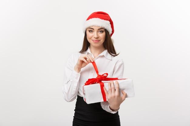 Koncepcja bożego narodzenia młoda szczęśliwa kaukaski kobieta biznesu z santa hat uśmiecha się, podczas gdy otwarte pudełko z kopią miejsca na boku