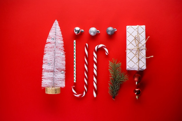 Koncepcja bożego narodzenia. prezent świąteczny, słodycze, gałązka sosny, zabawki na czerwono. leżał na płasko.
