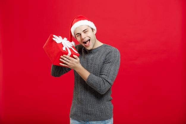 Koncepcja bożego narodzenia - przystojny młody mężczyzna w swetrze z czerwonym prezentem świątecznym.