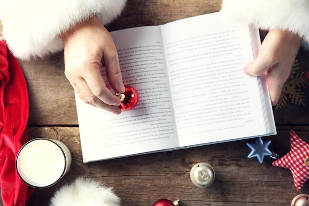 Koncepcja bożego narodzenia. ręce świętego mikołaja z książką i ozdobami świątecznymi na drewnianym stole, z bliska