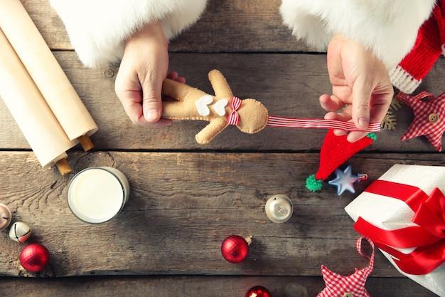 Koncepcja bożego narodzenia. święty mikołaj robi zabawkę, z bliska. ozdoby świąteczne na drewnianym stole.