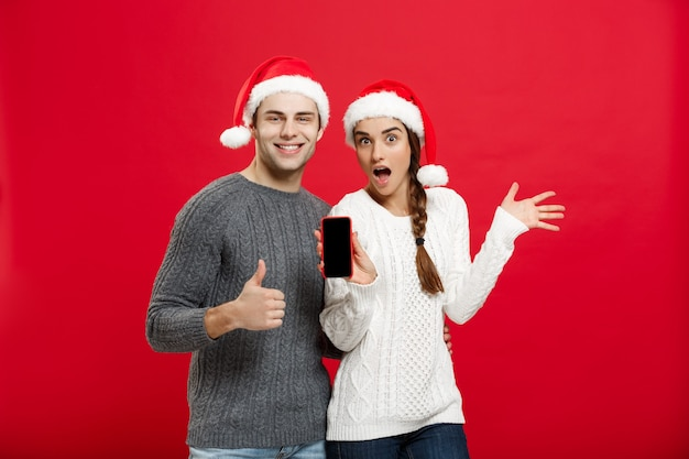 Koncepcja bożego narodzenia - szczęśliwa młoda para w boże narodzenie swetry pokazując uderzenie gestem z telefonu komórkowego.