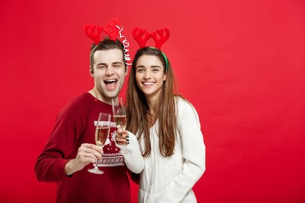 Koncepcja bożego narodzenia - szczęśliwa młoda para w swetry świętuje boże narodzenie z szampanem.