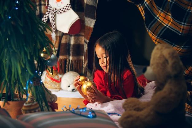 Koncepcja bożego narodzenia, wakacji i dzieciństwa - szczęśliwa dziewczyna w czerwonych ubraniach dekorujących naturalną jodłę