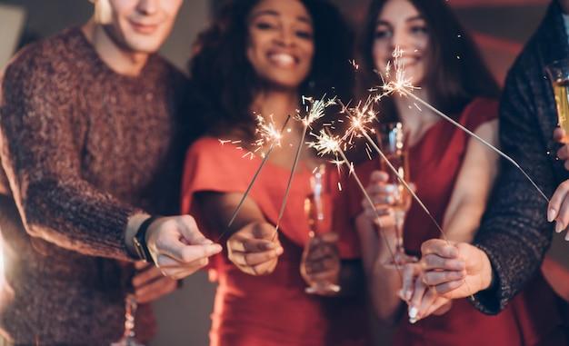 Koncepcja bożego narodzenia. wielorasowi przyjaciele świętują nowy rok i trzymają lampki bengalskie i szklanki z napojem