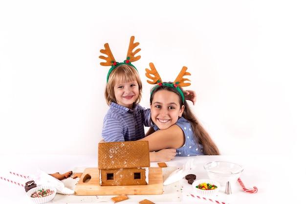Koncepcja bożonarodzeniowa dwoje dzieci robi domek z piernika na białym tle
