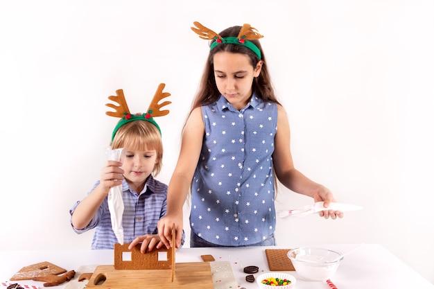 Koncepcja bożonarodzeniowa dwoje dzieci robi piernikowy domek na białym tle kartka świąteczna