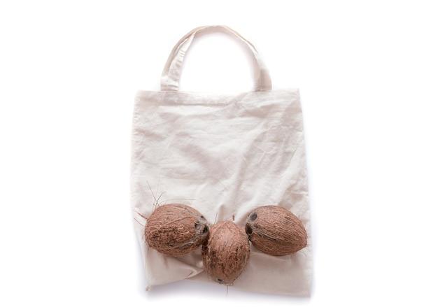 Koncepcja braku odpadów i plastiku. kokos na ekologicznej torbie na białej ścianie. leżał na płasko. skopiuj miejsce.