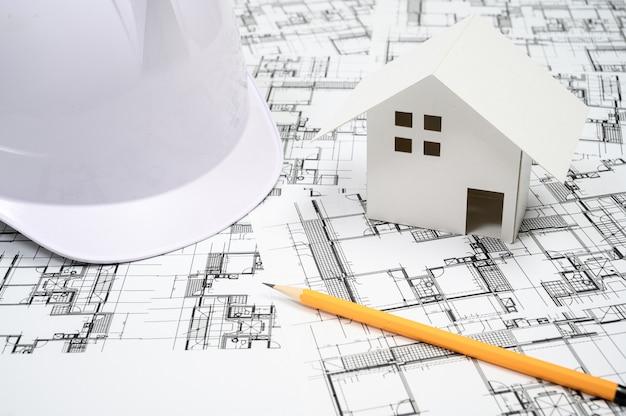 Koncepcja branży budowlanej z kask na rysunku architektonicznego