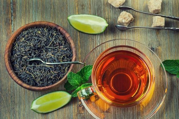 Koncepcja brytyjskiej herbaty na drewnianym biurku. aromatyczna herbata z tyłu podawana w przezroczystej filiżance z miętą, kwaśną limonką, zdrowym brązowym cukrem i dodatkowymi suszonymi ziołami.