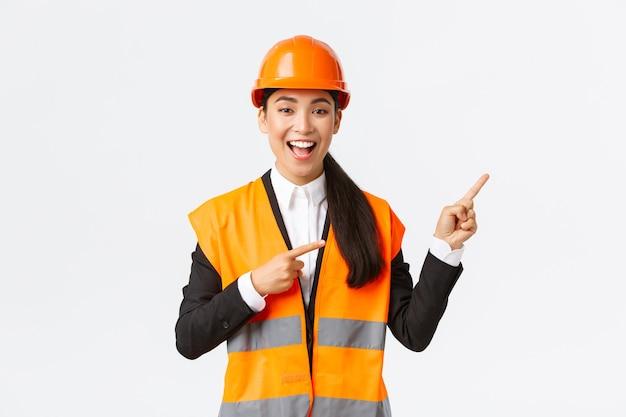 Koncepcja budowlano-przemysłowa. podekscytowana, pewna siebie, uśmiechnięta azjatycka agentka nieruchomości sprzedająca klientom dom, inżynier pokazujący projekt, architekt wskazujący palcami w prawym górnym rogu