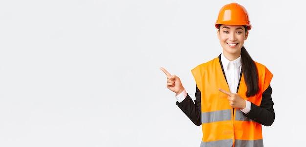 Koncepcja budowlano-przemysłowa. uśmiechnięta azjatycka architektka w kasku ochronnym, odblaskowa odzież wskazująca palec w lewym górnym rogu, pokazująca projekt w miejscu pracy, białe tło