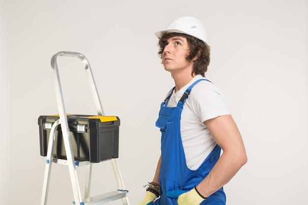 Koncepcja budowy, budynku i pracowników. kaukaski mężczyzna budowniczy sobie biały kask.