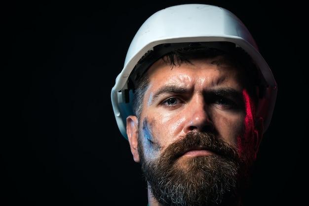 Koncepcja budynku biznesowego uśmiechnięty budowniczy w kasku portret pracownika mechanicznego z bliska