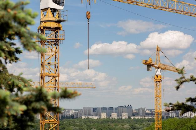 Koncepcja budynku niskiego: żurawie wieżowe przy budowie kamienicy na terenie parku