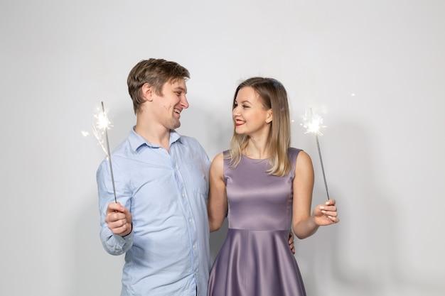 Koncepcja celebracja, impreza i wakacje - szczęśliwy mężczyzna i kobieta przytulanie na szarej ścianie z ogniskami.