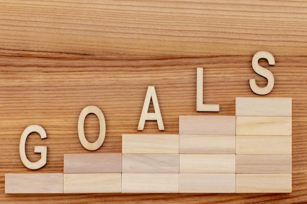 Koncepcja celów z drabiną sukcesu na drewnianym stole.