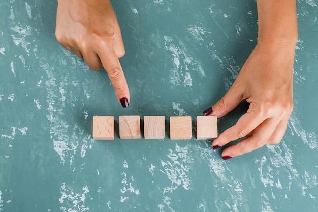 Koncepcja celu biznesowego. kobieta pokazuje i trzyma drewniane kostki.