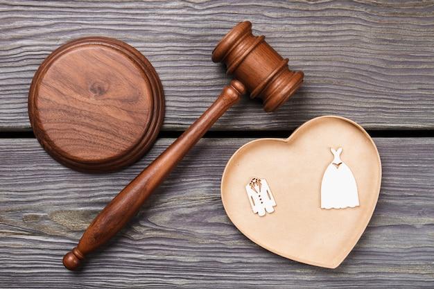 Koncepcja ceremonii ślubnej płasko świeckich. drewniany młotek i kostiumy na szarym stole.