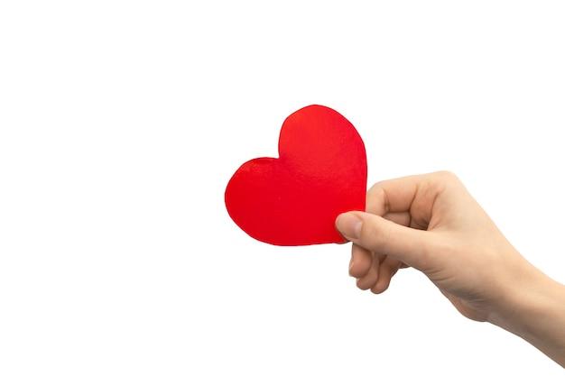 Koncepcja charytatywna. ręka trzyma czerwone serce na białym tle na białym tle. skopiuj zdjęcie miejsca