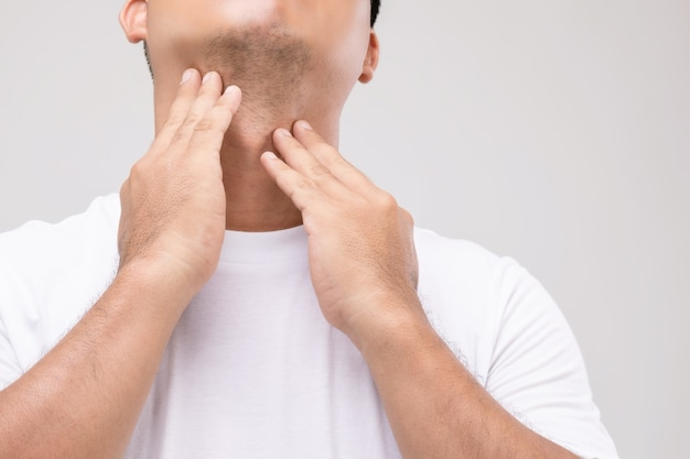 Koncepcja chłoniaka u mężczyzn: portret azjatycki mężczyzna dotyka szyi w pozycji węzła chłonnego.