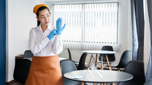 Koncepcja chore dom żony w skromnym stroju zakładającym lateksowe rękawiczki, aby chronić się przed zarazkami przed sprzątaniem pomieszczeń biurowych.