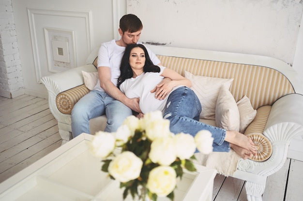 Koncepcja ciąży i ludzi. szczęśliwy człowiek tulenie swoją piękną ciężarną żonę w domu. przyszli rodzice czekają na nienarodzone dziecko.