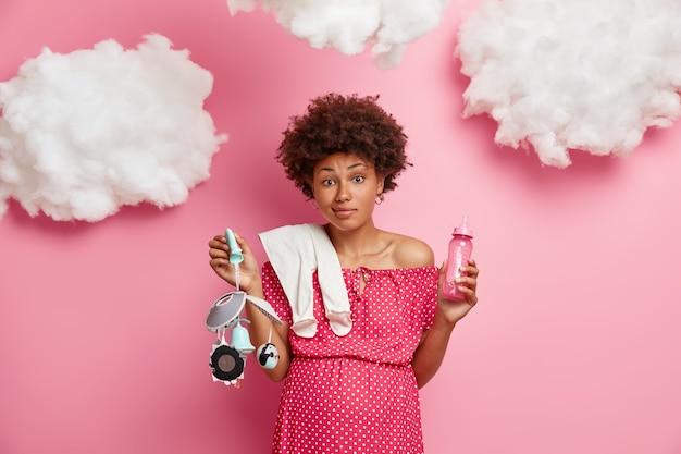 Koncepcja ciąży i macierzyństwa. zdezorientowana ciężarna kręcona kobieta trzyma rzeczy dla nienarodzonego dziecka, przygotowuje się do urodzenia dziecka, pozuje na różowej ścianie z chmurami. przyszła mama z brzuchem