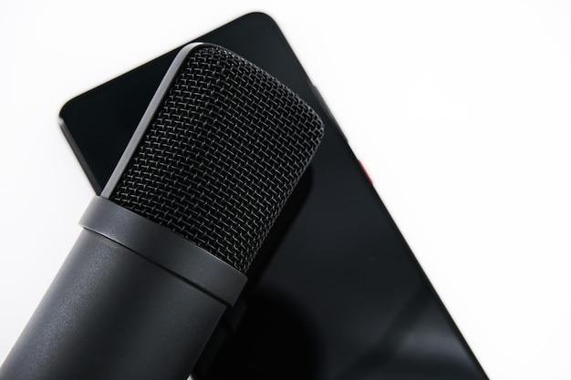 Koncepcja clubhouse drop-in audio to aktywowana głosem aplikacja społecznościowa. smartfon i mikrofon na białej ścianie