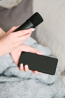 Koncepcja clubhouse drop-in audio to aktywowana głosem aplikacja społecznościowa. smartfon i mikrofon w rękach kobiet na lekkiej ścianie