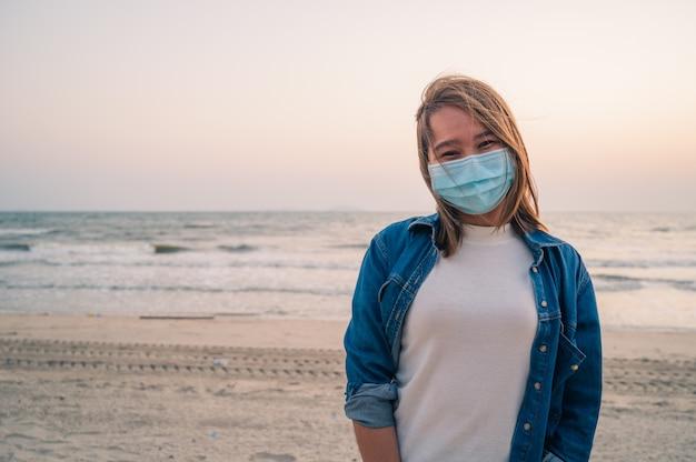 Koncepcja covid-19, azjatycka młoda kobieta ubrana w higieniczną maskę ochronną na twarzy na zewnątrz z zachodem słońca na plaży