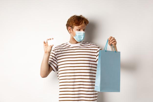 Koncepcja covid-19 i stylu życia. wesoły młody człowiek z rudymi włosami, nosić maskę medyczną, pokazuje torbę na zakupy ze sklepu i plastikową kartę kredytową.