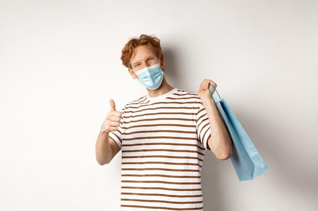 Koncepcja covid-19 i zakupy. zadowolony młody człowiek wyglądający na zadowolonego po zakupach, noszący maskę, pokazujący kciuki do góry, polecający sklep, białe tło.