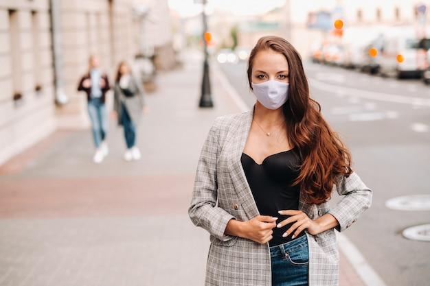 Koncepcja covid-19 i zanieczyszczenia powietrza pm2,5. pandemia, portret młodej kobiety w masce ochronnej na ulicy. pojęcie bhp.