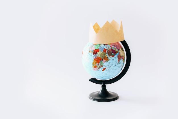 Koncepcja covid 19. jeden globus z koroną na nim, lekki stół.