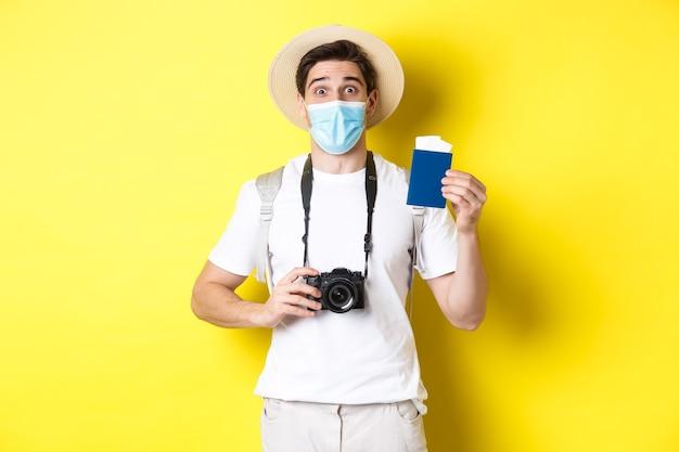 Koncepcja covid-19, podróżowanie i kwarantanna. szczęśliwy człowiek turysta z aparatem, pokazując paszport i bilety na wakacje, udaje się w podróż podczas pandemii, żółte tło.