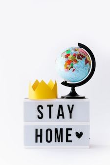 Koncepcja covid 19. tekst stay home na wyświetlaczu w lightboxie i globusie z koroną, podświetlany stół.
