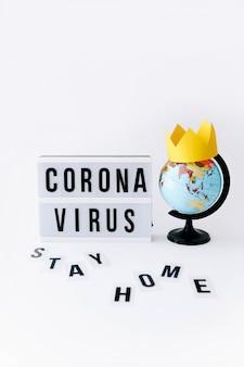 Koncepcja covid 19, tekst wirusa corona na wyświetlaczu w lightbox i kula ziemska z koroną, podświetlany stół.