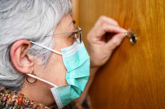 Koncepcja covid-19. zostań w domu. samoizolacja, aby zapobiec pandemii koronawirusa. starszy kobieta w ochronne zielone maski wygląda przez wizjer.