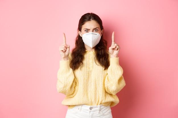 Koncepcja covid, corona i dystansu społecznego. zdezorientowana i zszokowana młoda kobieta w respiratorze, wskazująca palcami w górę, wpatrująca się zaskoczona w kamerę, różową ścianę.