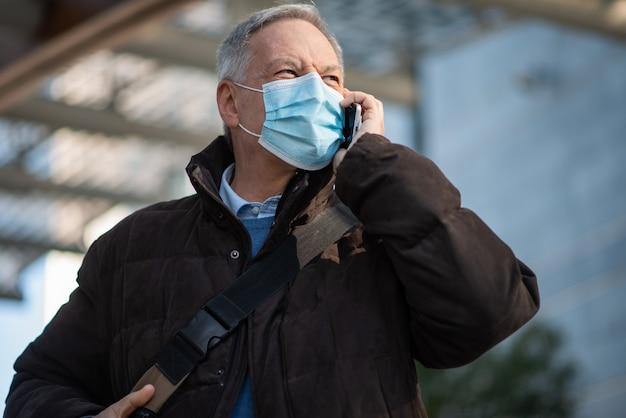 Koncepcja covid koronawirusa, zamaskowany starszy biznesmen rozmawiający na swoim smartfonie na świeżym powietrzu